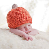 newborn in a cap pumpkin — Stock Photo