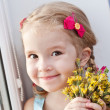 Beautiful little girl with flowers — Stock Photo #33164717