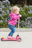 Kleinkind mädchen auf einem scooter in einem park — Stockfoto