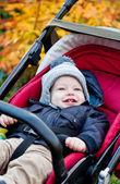 Lycklig pojke som sitter i en barnvagn — Stockfoto
