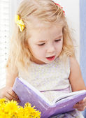 Cute little girl reading — Stok fotoğraf
