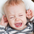 Cute little boy crying holding his ear — Stock Photo