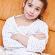 Adorable girl in pajamas sitting — Stock Photo