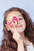 Cute little girl eating a lollipop — Stock Photo