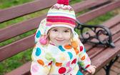 Cute little girl sitting on the bench — Foto de Stock