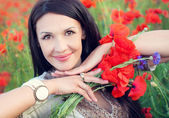 Ukrainian brunette woman with a bouquet of poppies — Стоковое фото