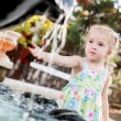 Cute little preschooler girl playing with a city fountain — Stock Photo #51387563