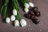 White Tulips with Sated Chocolate Candies — Stock Photo