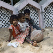 Three poor slum children playing on sand — Stock Photo
