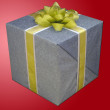 A gift box wrapped in silver grey and tied with yellow ribbon isolated on red background — Stock Photo #37125279