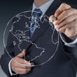 Businessman hand drawing abstract globe — Stock Photo #18387229