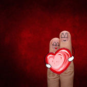 A happy couple in love with painted smiley and hold heart — Stock Photo