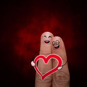 Happy finger couple in love with painted smiley and hold heart — Stock Photo