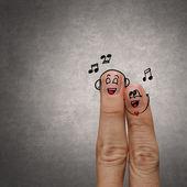 Pár šťastný prst v láska s malovanými smajlík a zpívat píseň — Stock fotografie