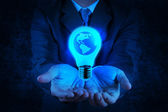 Businessman hand shows Light bulb with planet Earth — Zdjęcie stockowe