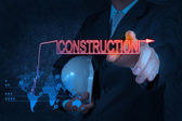 Businessman hand pointing to construction — Stock Photo