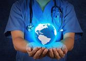 Врач держит глобус мира в руках как медицинской сети — Стоковое фото