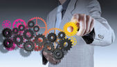 Businessman hand makes colorful gear to success — Stock Photo