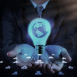 Businessman hand shows Light bulb with planet Earth  — Stock Photo
