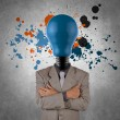 Businessman with lamp-head and splash colors — Stock Photo