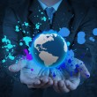 Businessman holding a glowing earth globe in his hands and splas — Stock Photo #30941841