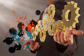 Businessman working with gear and splash colors — Stock Photo