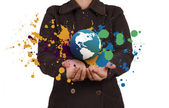 Businesswoman shows the earth and splash colors — Stock Photo