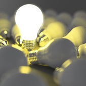 Growing light bulb standing out from the unlit incandescent bulb — Stockfoto