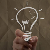 Hand drawing light bulb with crumpled paper — Stock Photo