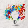 Invisible light bulb and splash colors on crumpled paper — Stock Photo
