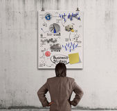 Businessman looking business concept on poster wall — Stock Photo