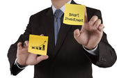 Businessman hand showsmart investment words on sticky note with — Stock Photo