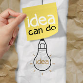 Hand holding sticky note with idea can do word light bulb on cr — Stock Photo