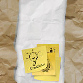 Sticky note with light bulb on crumpled paper as creative conce — Stock Photo