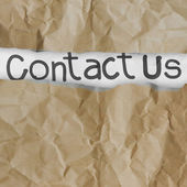 Hand drawn contact us words on crumpled paper with tear envelop — Stock Photo
