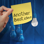 Hand holding sticky note with another idea light bulb on crumple — Stock Photo