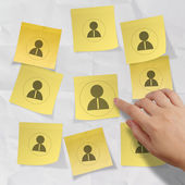 Hand pushing sticky note social network icon on crumpled paper — Stock Photo