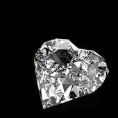 Diamond heart shape on black surface — Stock Photo