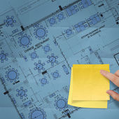 Blank sticky note on construction site with layout plan crumpled — Stock Photo