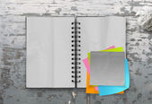 Sticky notes with open blank note book on desk top texture — Stock Photo
