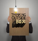 Man showing poster of hand drawn word THINKING OUTSIDE OF THE BO — Stock Photo