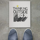 design word THINKING OUTSIDE OF THE BOX  on canvas board on fro — Stock Photo