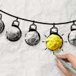 Hand drawn light bulb on wire doodle with crumpled paper as lead — Stock Photo