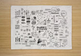 Hand drawn business strategy on crumpled paper and wooden  backg — Stock Photo