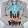 Businessman hand holding 3d house with family icon as insurance — Stock Photo #47399705