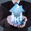 Businessman hand holding 3d house with family icon as insurance — Stock Photo #47399709