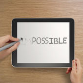 Hand changing the word impossible to possible with stylus eraser — Stock Photo
