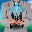 Businessman hand holding 3d house with family icon as insurance — Stock Photo #49357693