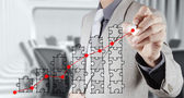 Businessman hand puzzle charts with new modern computer and busi — Stockfoto