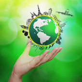Hand showing airplane traveling around the world on green nature — Stock Photo